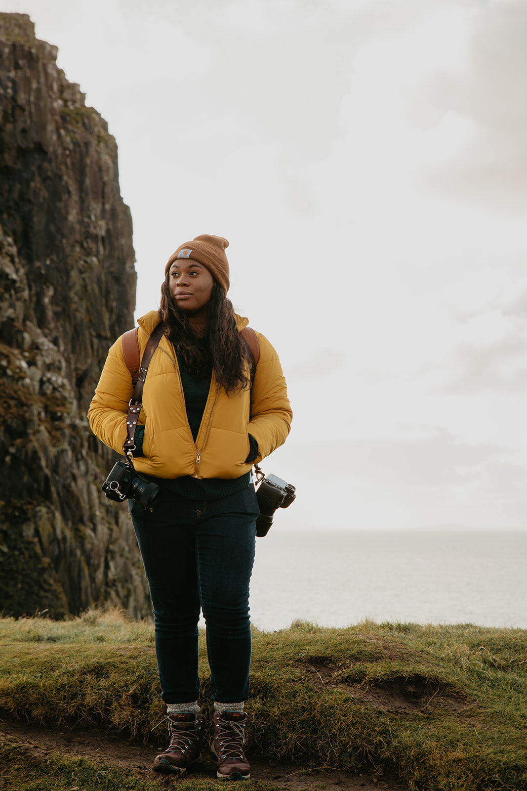 Photographer standing at Neist Point in Scotland wearing a yellow jacket